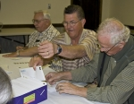 Bob Stimmel, Dick Gray, and Pete King putting their all into labeling envelopes.